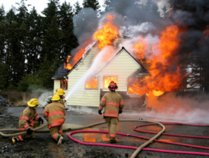 "ALT=""homeowner's accident liability in a burning house being extinguished by firefighters, blog post image for Insurance Problem Solver and Luke Brown"""